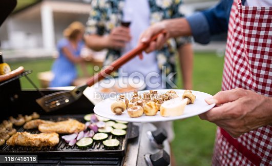 A midsection of family outdoors on garden barbecue, grilling.