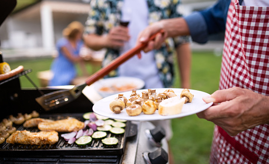 istock Midsection of family outdoors on garden barbecue, grilling. 1187416118