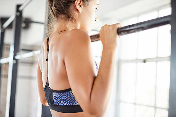 Midsection of female exercising on pull-up bar in gym – Foto