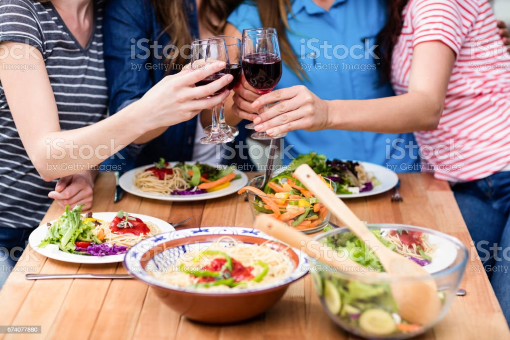 Midsection of friends toasting red wine glasses royalty-free stock photo