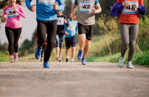 mittelteil einer großen gruppe von menschen, die einen rennwettbewerb in der natur laufen. - laufveranstaltungen stock-fotos und bilder
