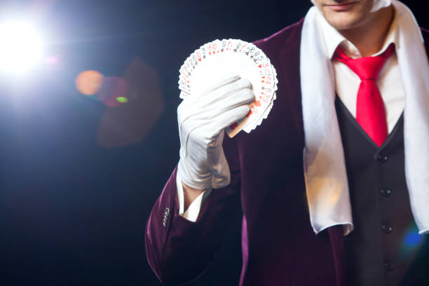 Midsection of magician showing fanned out cards against black background. Magician, Juggler man, Funny person, Black magic, Illusion close-up Midsection of magician showing fanned out cards against black background. Magician, Juggler man, Funny person, Black magic, Illusion. magic trick stock pictures, royalty-free photos & images