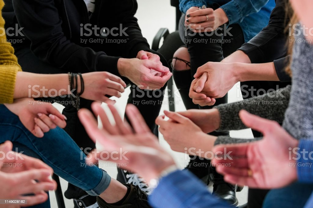 Midsection of male therapist with young students Midsection of young university students and mental health therapist. High angle view of professional is with men and women. They are in group therapy at lecture hall. 18-19 Years Stock Photo
