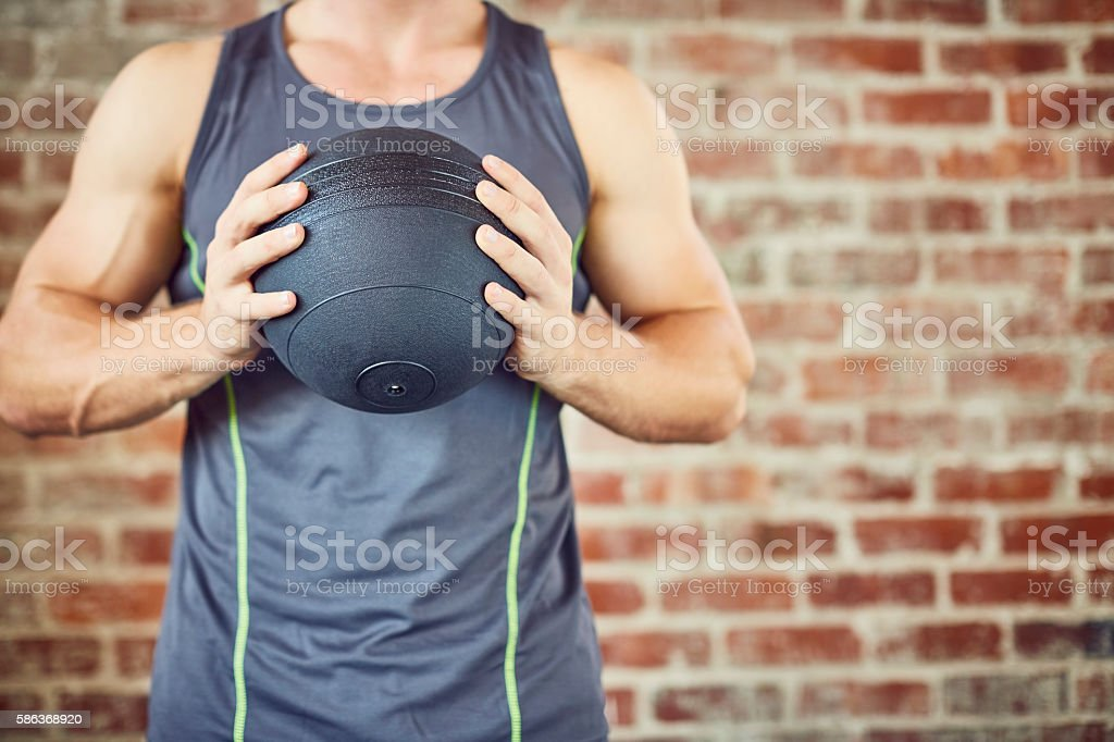 Midsection of man holding medicine ball in gym stock photo