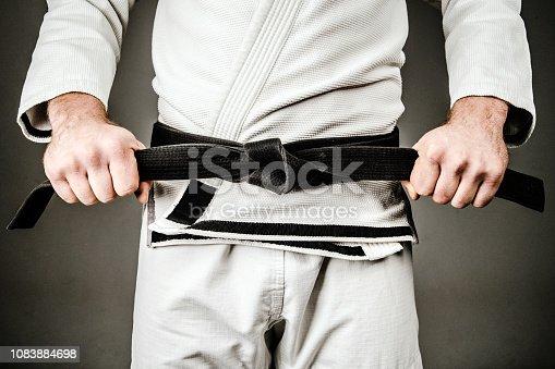 Man in White BJJ Brazilian Jiu JItsu Judo Gi Holding Black Belt. Close Up. Martial Arts, Fighter, BJJ, Ne Waza, Karate