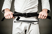 Midsection of Man in A Gi holding Black Belt