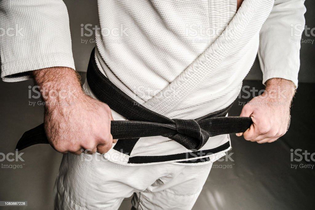 Midsection of Man in A Gi holding Black Belt stock photo