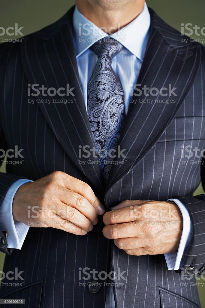 Midsection Of Man In Suit Buttoning Button On Coat stock photo