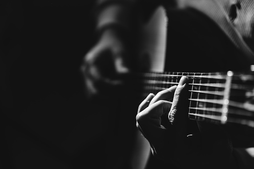 B&W photo of midsection of man holding a classical guitar, playing music