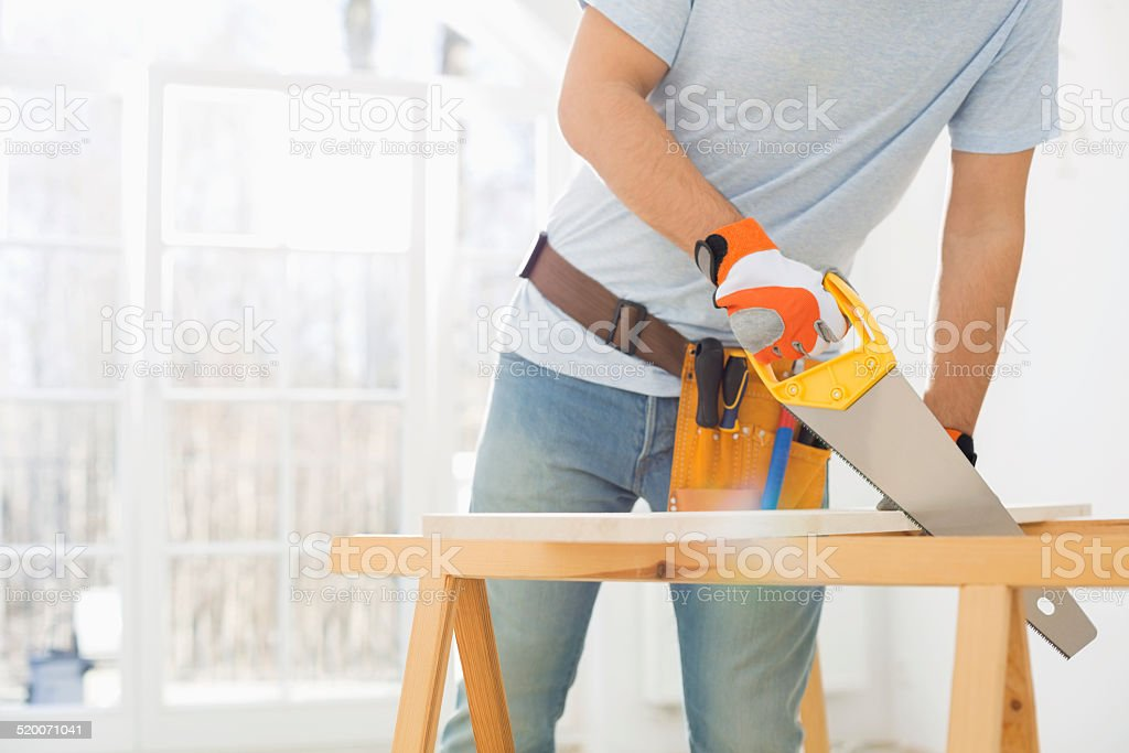 Midsection of man sawing wood in new house stock photo