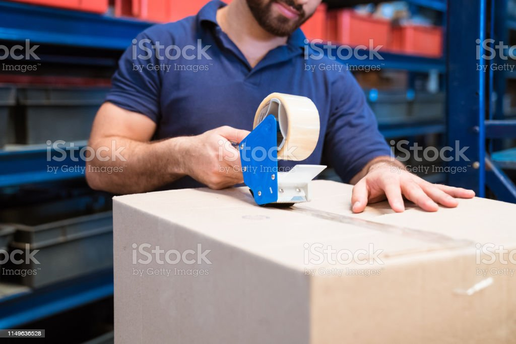 Midsection of manual worker packing cardboard box Midsection of manual worker packing cardboard box. Laborer is working in distribution warehouse. He is using tape dispenser. 20-24 Years Stock Photo