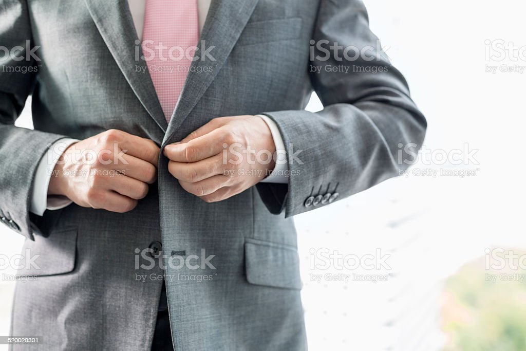Midsection of mature businessman buttoning his blazer stock photo