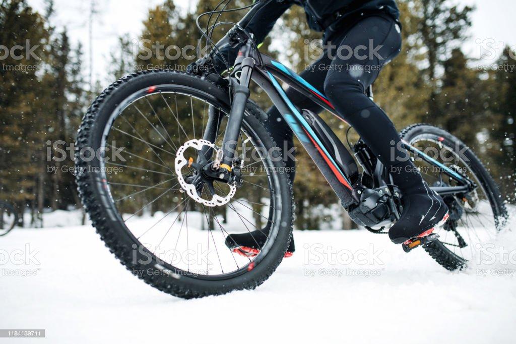 Mittelteil der Mountainbiker reiten im Winter im Schnee im Freien. - Lizenzfrei Abenteuer Stock-Foto