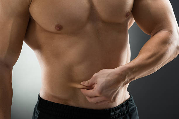 Midsection Of Muscular Man Holding Fat Belly - foto de acervo