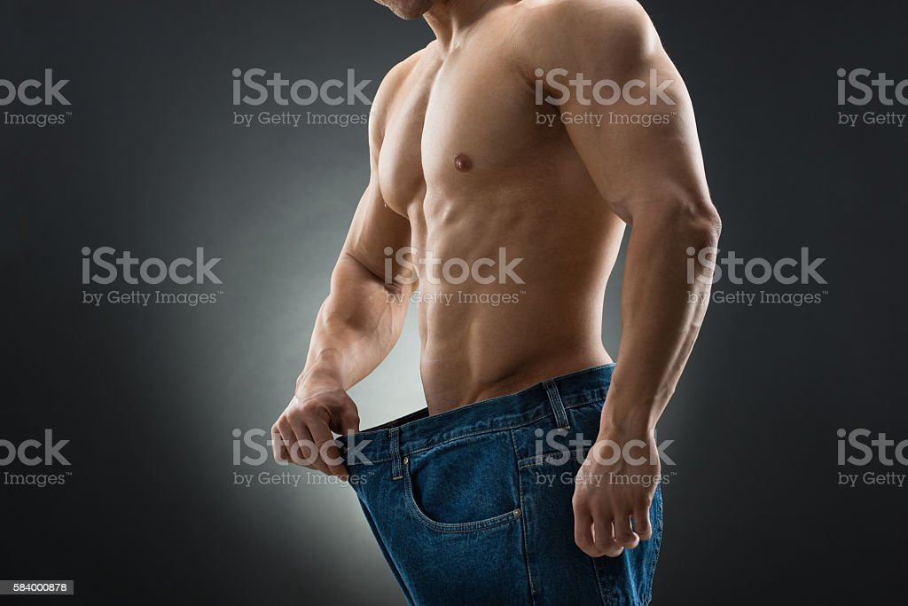Midsection Of Muscular Man In Old Jeans Showing Weight Loss stock photo