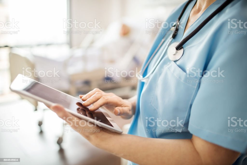 Midsection of nurse using tablet pc in hospital stock photo