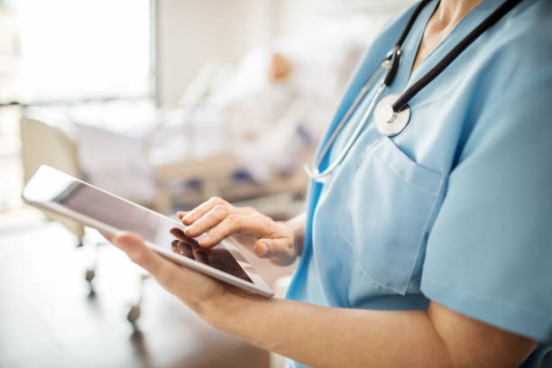 midsection of nurse using tablet pc in hospital - midsection stock pictures, royalty-free photos & images