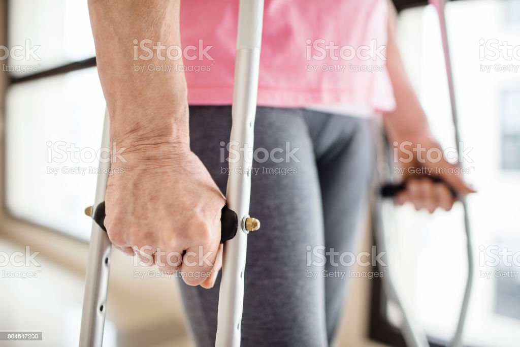 Midsection of patient with crutches in hospital stock photo