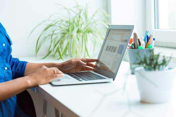 Midsection of pregnant businesswoman using laptop stock photo
