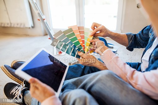 Senior couple with tablet painting new home, looking at color swatch. A relocation concept.