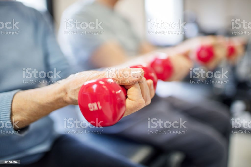 Midsection of senior woman lifting dumbbells stock photo