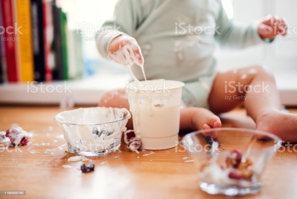 A midsection of small messy toddler boy sitting on kitchen counter at...
