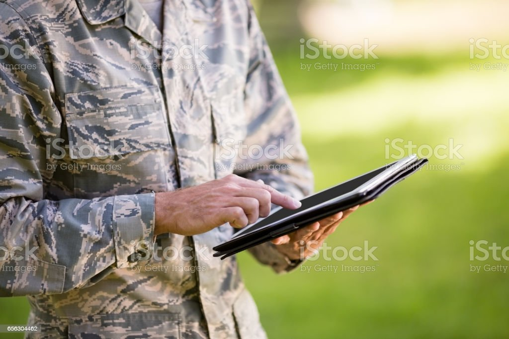 Mid-section of soldier using digital tablet in park stock photo