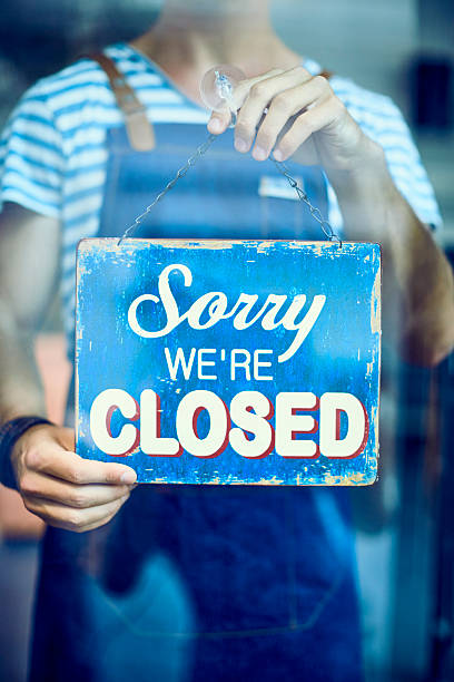 Midsection of waiter holding closed sign at window – Foto