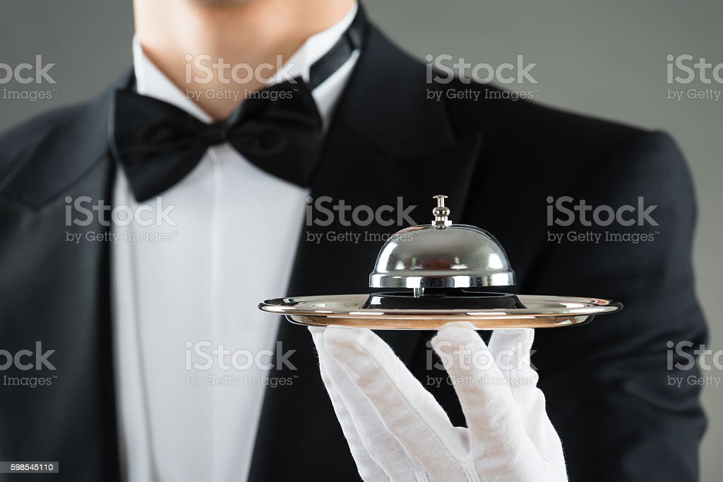 Midsection Of Waiter Holding Service Bell In Plate stock photo