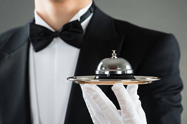 Midsection Of Waiter Holding Service Bell In Plate - foto de stock