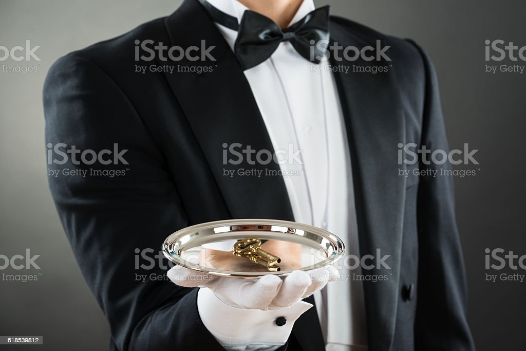 Midsection Of Waiter Holding Tray With Keys stock photo