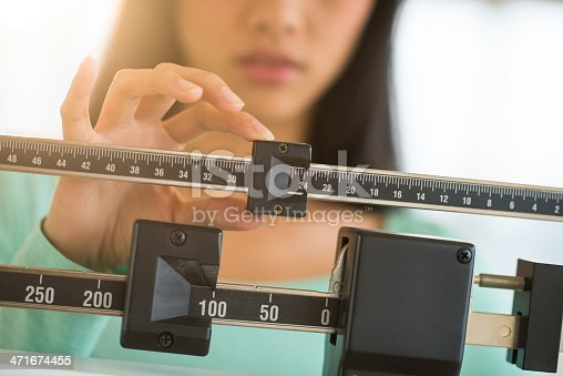 Midsection of mid adult Asian woman adjusting balance weight scale