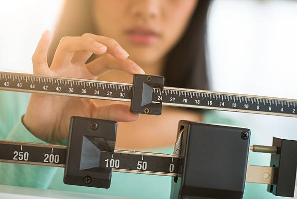 midsection of woman adjusting weight scale - scale stock photos and pictures
