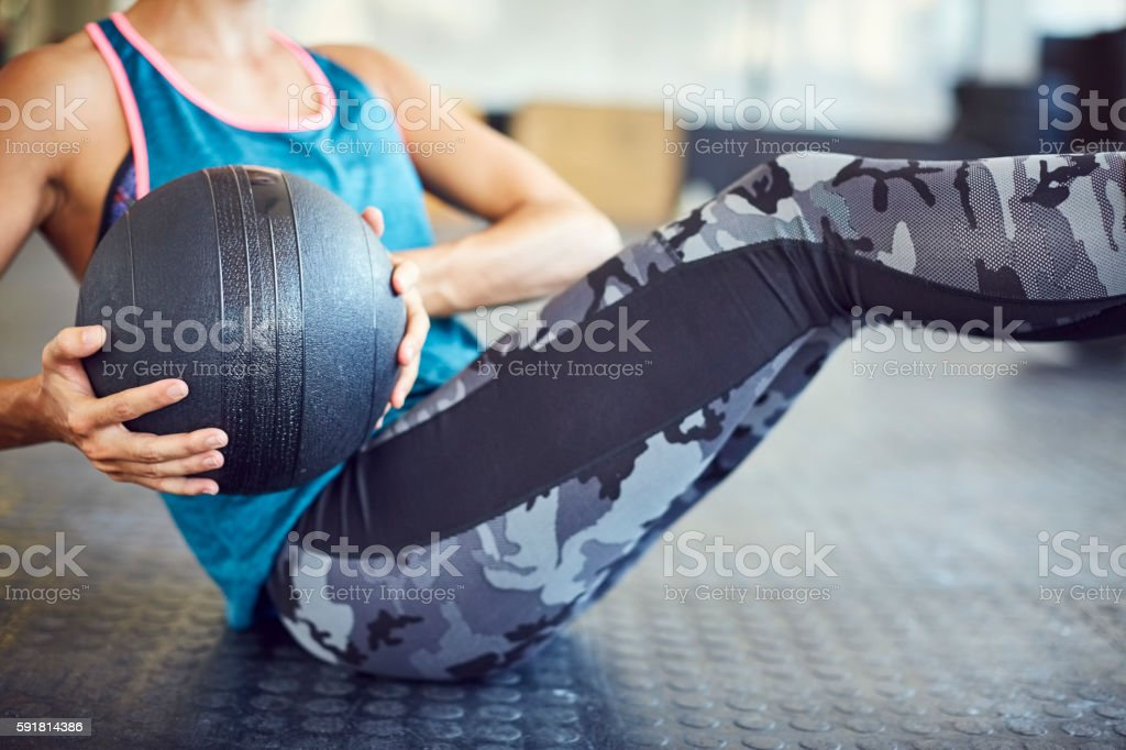 Midsection of woman exercising with medicine ball in gym – Foto