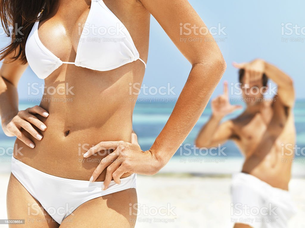 Bauchgegend von Frau trägt einen bikini am Strand Lizenzfreies stock-foto