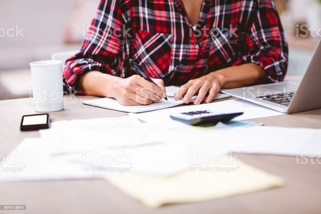 Midsection of woman writing in notepad royalty-free stock photo