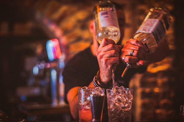 Tronco de jovem barman preparar cocktails no bar de vida noturna - foto de acervo