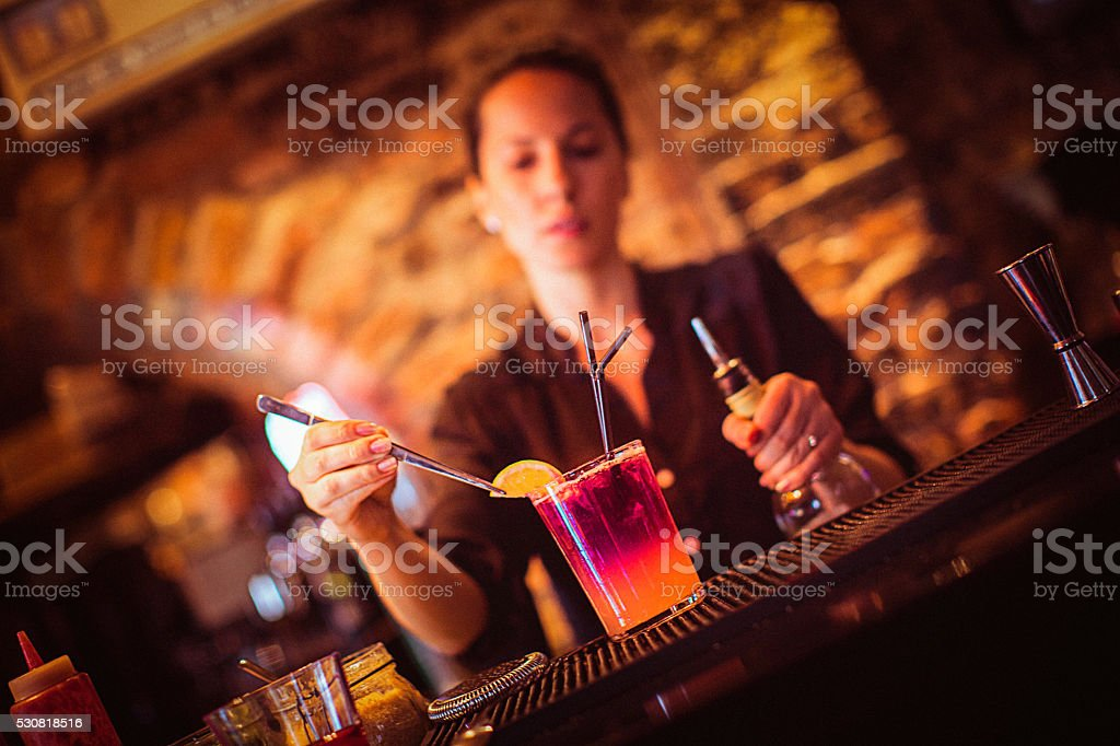 Midsection of young female bartender preparing cocktail in cocktail bar stock photo