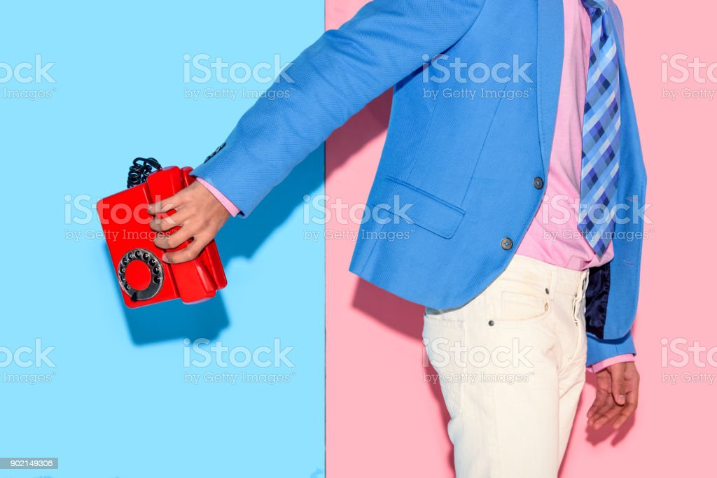 Midsection of young man in jacket with retro phone in hand stock photo