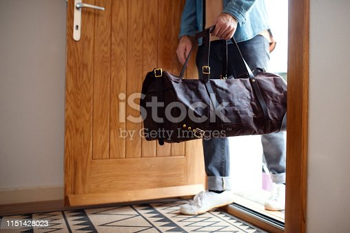 istock Midsection of young man with bag entering front door when coming back home. 1151428023