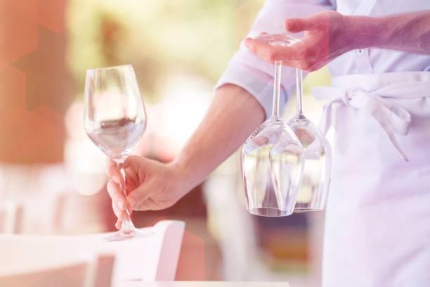 Mittelteil des jungen Kellners, der Weingläser auf dem Tisch im Restaurant arrangiert – Foto