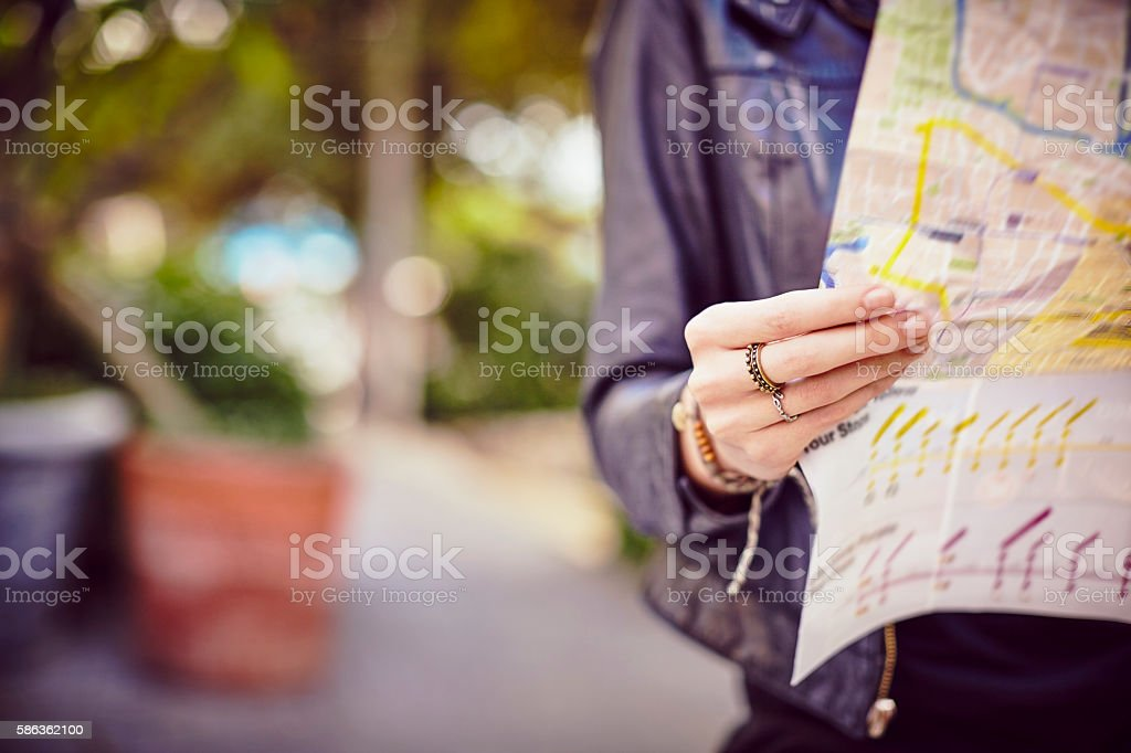 Midsection of young woman holding city map on street stock photo