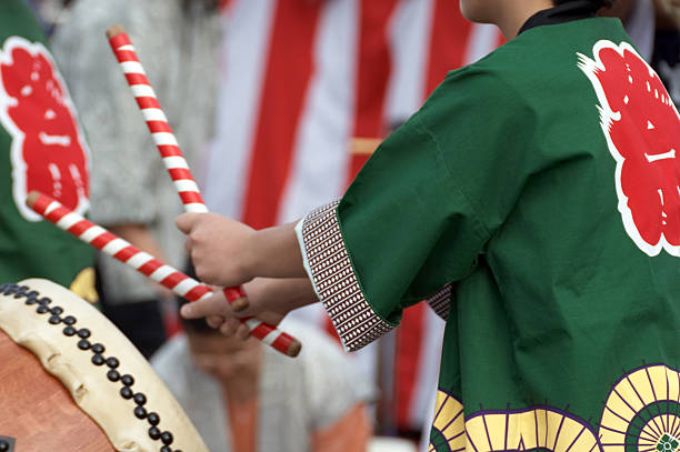 Midsection rear view of a child playing the Taiko drums