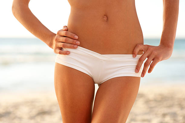 Midsection view of a sexy woman standing at beach stock photo