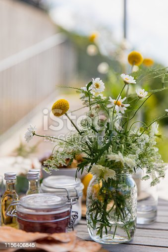 Flowers and herring and marmalade on a table during midsummer.
