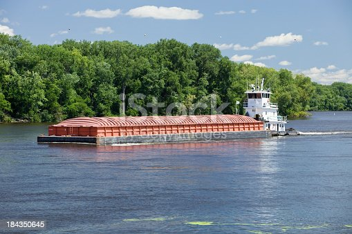 A tow is pushing a barge up the Mississippi River. This single barge will be connected with others for a longer haul.