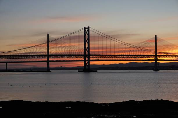 Midsummer sunset behind road Bridges over the Forth stock photo