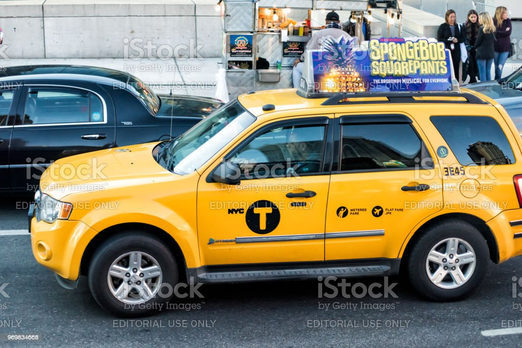 Midtown Manhattan NYC NY with street road, yellow taxi cab cars in traffic, Spongebob Squarepants musical ad