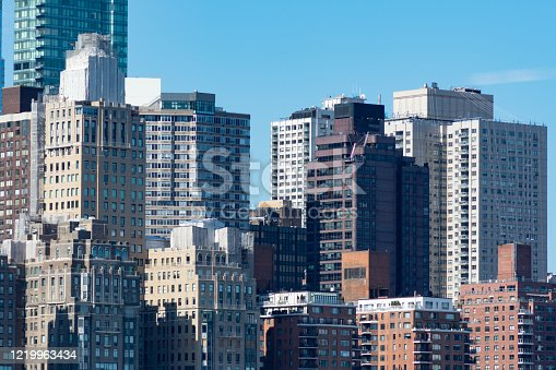 A variety of old and new skyscrapers and buildings in the Midtown Manhattan skyline with a clear blue sky in New York City