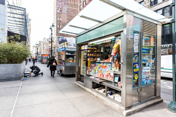 Midtown Manhattan with street sidewalk on Broadway, Newsstand with newspaper, magazines, candy New York City, USA - April 7, 2018: Midtown Manhattan with street sidewalk on Broadway, Newsstand with newspaper, magazines, candy news stand stock pictures, royalty-free photos & images